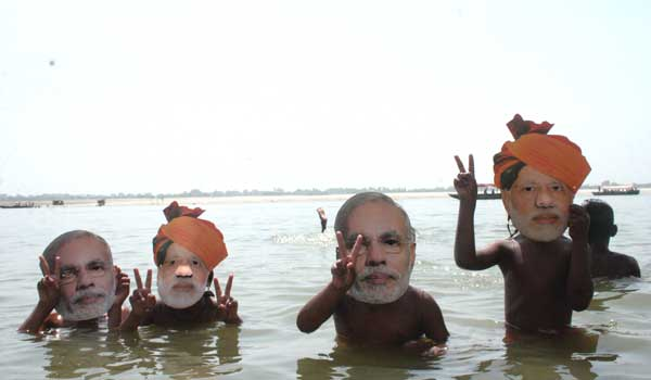 Children take bath wearing masks of BJP Prime Ministerial candidate Narendra Modi in the Ganga river in Varanasi on May 20, 2014.