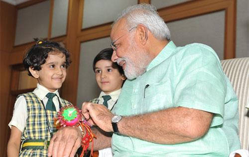Children tying 'Rakhi' to the Prime Minister, Shri Narendra Modi, on the occasion of 'Raksha Bandhan'