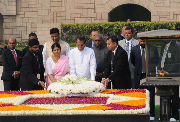 The President of the Democratic Socialist Republic of Sri Lanka, Maithripala Sirisena and Jayanthi Sirisena laying wreath at the Samadhi of Mahatma Gandhi, at Rajghat, in Delhi on February 16, 2015. The Minister of State for Road Transport & Highways and Shipping, P. Radhakrishnan is also seen.