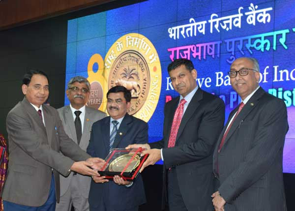 Right to left  S.S. Mundra,  Deputy Governor RBI, Raghuram Rajan, Governor RBI, conferring Rajbhasha Shield and certificate of Merit to Gauri Shankar MD & CEO Punjab National Bank.  Also seen in the picture are Vivek Jha, Field General Manager Mumbai and Premchand Sharma, AGM Rajbhasha HO