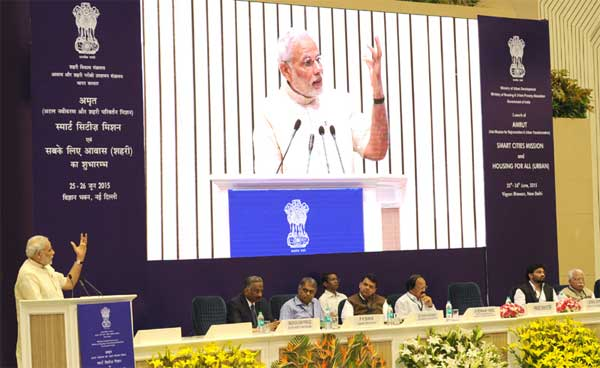 The Prime Minister, Narendra Modi addressing at the launching ceremony of the Smart Cities Mission, Atal Mission for Rejuvenation and Urban Transformation (AMRUT) and Housing for All Mission, in New Delhi on June 25, 2015. The Union Minister for Urban Development, Housing and Urban Poverty Alleviation and Parliamentary Affairs, M. Venkaiah Naidu, the Chief Minister of Haryana, Manohar Lal Khattar, the Chief Minister of Maharashtra, Devendra Fadnavis, the Minister of State for Urban Development, Housing and Urban Poverty Alleviation, Babul Supriyo, the Cabinet Secretary, Pradeep Kumar Sinha and the Secretary, Ministry of Urban Development,  Madhusudhan Prasad are also seen.