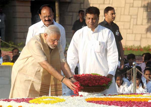 The Prime Minister, Narendra Modi paying floral tributes at the Samadhi of Mahatma Gandhi on his 146th birth anniversary, at Rajghat, in Delhi on October 02, 2015. The Union Minister for Urban Development, Housing and Urban Poverty Alleviation and Parliamentary Affairs, M. Venkaiah Naidu is also seen.