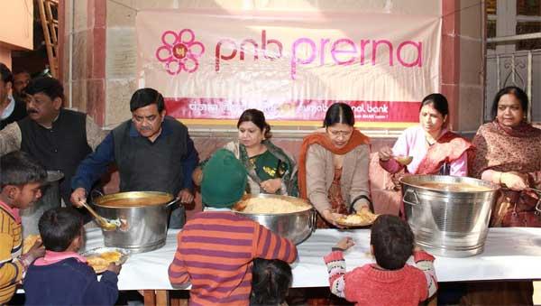Gauri Shankar, ED is seen distributing food in the Anna Dan Seva along with Sunita Rani Gupta, Vice President, PNB Prerna and other members of PNB Prerna.