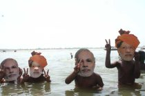 Children take bath wearing masks of BJP Prime Ministerial candidate Narendra Modi in the Ganga river in Varanasi on May 20, 2014.