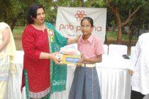 Rashima Chaudhary, Chairperson, PNB PRERNA, South Delhi Circle  distributing shoes and socks to the unpriviledged students