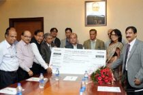 The Minister for Mines and Steel, Narendra Singh Tomar receiving the dividend cheque from the CMD, NALCO, Ansuman Das