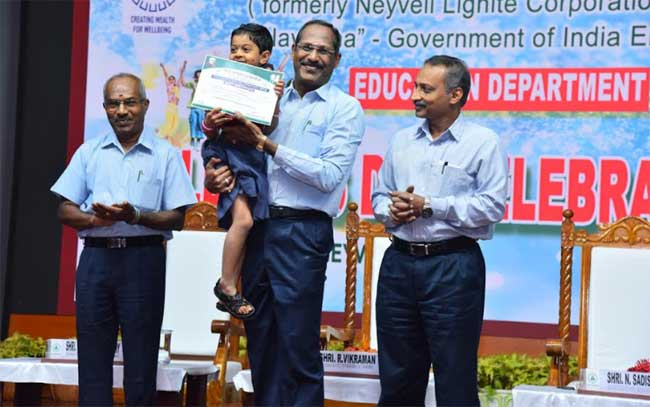 Shri R.Vikraman, Director (HR), NLCIL appreciating a child, who won first prize in the Fancy Dress Competition, at the Children's Day celebration organized by Education Department of NLC India Ltd., Also seen are Shri N.Sadish Babu, Exe. Director/HR and Shri Vinayagamurthy, GM/Education (Left Extreme), NLCIL
